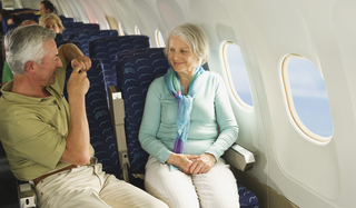 Healthy older couple enjoying holiday on aeroplane